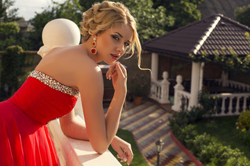 beautiful woman with blond hair in luxurious dress at villa