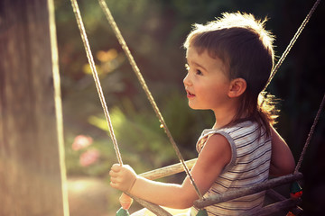 boy in the sun on a swing