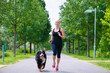 Sports outdoor - young woman running with dog in park