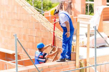 Handwerker kontrollieren Wände auf Baustelle