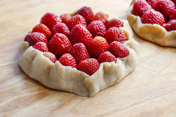 Strawberry tart before baking on wooden table