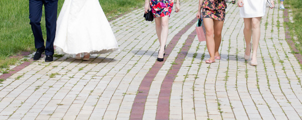 Bride, groom and female guests on city pavement