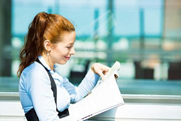 Portrait businesswoman reading magazine in corporate office
