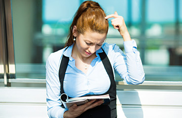 Business woman reading magazine, financial report, confused