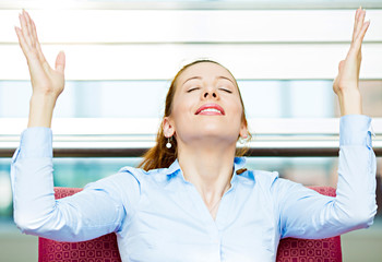 Happy business woman relaxing in armchair in corporate office