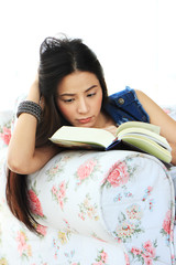 Tired young woman reading a book at home on sofa.