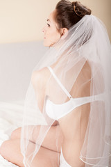 Attractive bride in bedroom with white veil