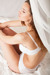Half-naked sexy woman sitting on bed