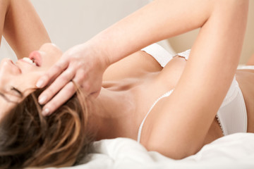 Seductive and happy woman lying in bed and touching her hair