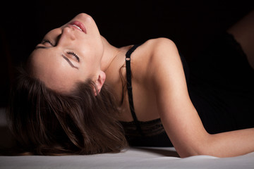 Woman in sexy nightwear lying on her back