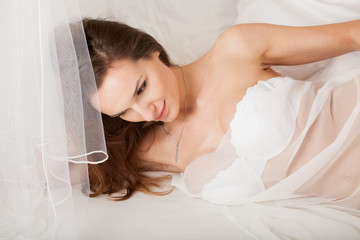 Lady lying in bed wrapped in transparent material