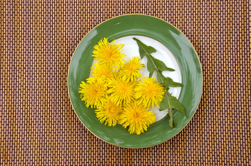 fresh spring dandelion leaf and flowers in plate