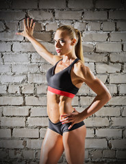 Muscular woman on brick wall background (normal version)