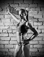 Muscular woman on brick wall background (monochrome version)