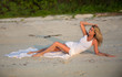 Beautiful woman in white dress lying on the beach