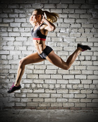 Muscular jumping woman on brick wall background (dark version)