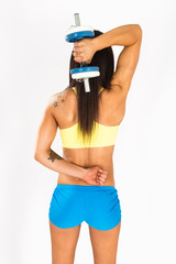 Muscular young girl with dumbbells