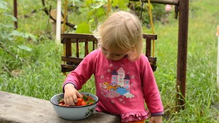 Cute Little Girl Eating Strawberry in Green Garden