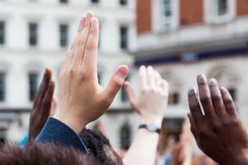 Menschen heben ihre Hände zur Abstimmung