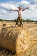 Boy stands on bale straw