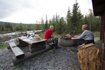 couple having a picnic near a strem