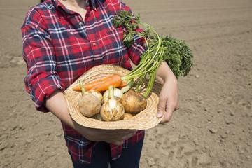収穫の野菜を持つ女性
