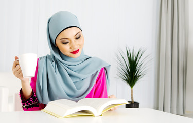 Muslim woman reading and having a cup of tea at home