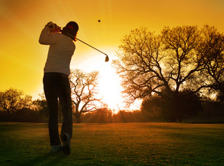 golfer play stroke into setting sun