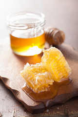 honeycomb dipper and glass jar on wooden background