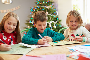 Three Children Writing Letters To Santa Together