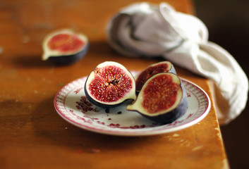 Fresh ripe juicy figs halved on a dessert plate