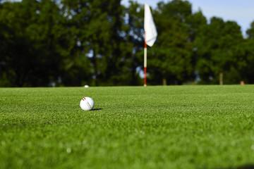 Ein Golfball und das Ziel die Fahne