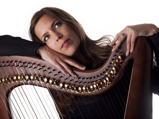 beautiful brunette leaning on her classical harp