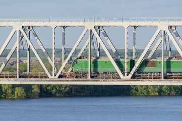 green electric locomotive passing the bridge over the river in s