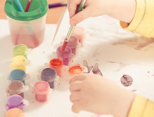 little boy arm with tassel in paint