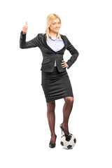 Businesswoman standing on a football
