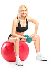 Female athlete exercising with dumbbell