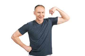 older man flexing muscles and smiling.