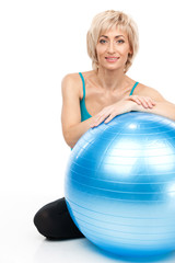 blond lady sitting behind fitness ball.