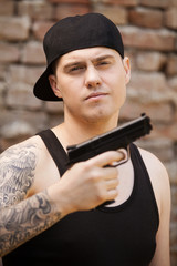young guy with tattoo holding gun.