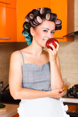 middle-aged woman housewife in the kitchen with apple