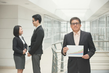 senior asian business ceo showing positive report with team on b