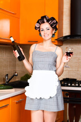 middle-aged housewife in kitchen with bottle and glass of wine
