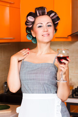 middle-aged housewife in the kitchen with glass of wine
