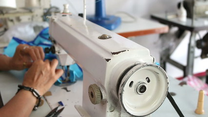Closeup shot of sewing machine with the hands of a tailor