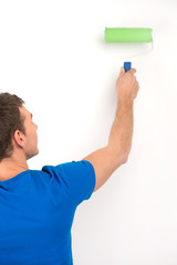 young man painting wall in green.