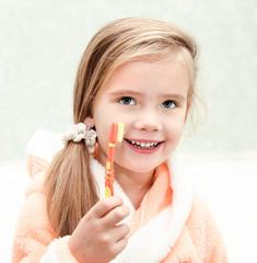 Smiling cute little girl brushing teeth