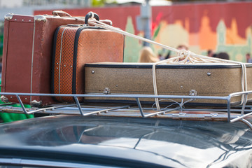 old suitcases on a luggage carrier on the roof of an ancient car