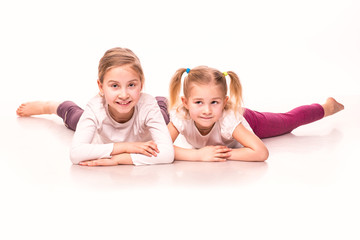 Sportive girls on a floor isolated over white