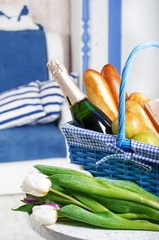 Blue basket with shampagne and tulips in the blue interior